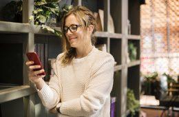 Frau, die lächelnd auf ihr Handy schaut