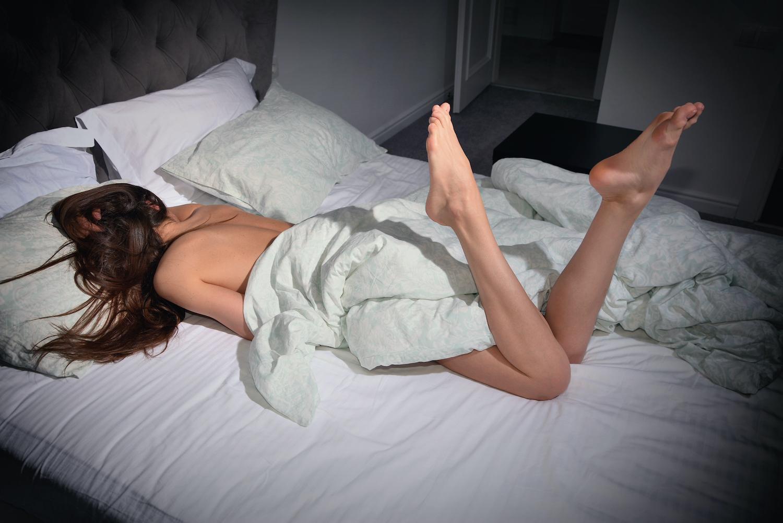 Frau im zerwühlten Bett als Symbolbild für Orgamsus
