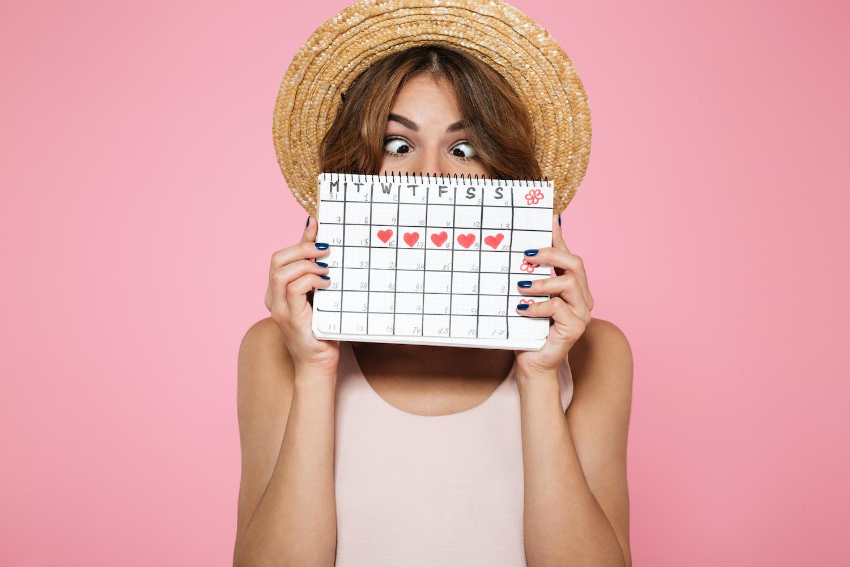 Frau hält Kalender hoch, Tage der Regel mit Herzen eingezeichnet