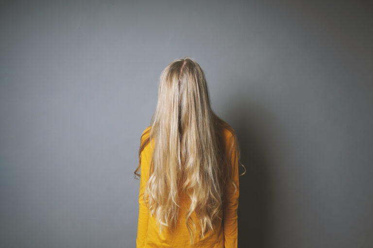 Frau mit über dem Gesicht hängenden Haaren