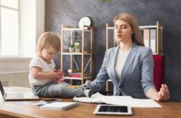 Frau meditiert, Baby sitzt vor ihr am Tisch
